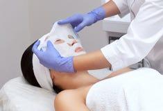 Cosmetologisten för tillvägagångssättet av att rentvå och att fukta huden som applicerar en arkmaskering till framsidan fotografering för bildbyråer