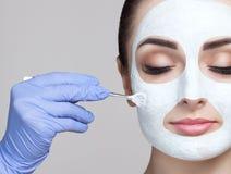 Cosmetologisten för tillvägagångssättet av att rentvå och att fukta huden som applicerar en maskering med pinnen till framsidan royaltyfri bild