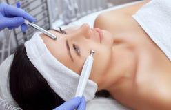 Cosmetologisten gör apparaturen ett tillvägagångssätt av Microcurrent terapi av en härlig ung kvinna i en skönhetsalong arkivbilder
