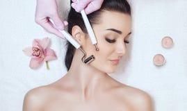 Cosmetologisten gör apparaturen ett tillvägagångssätt av Microcurrent terapi av en härlig ung kvinna i en skönhetsalong arkivbild