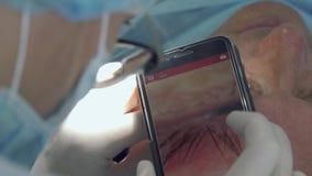 Cosmetologisten gör makrofotoet på telefonen för undersökande hud, når han har tagit bort vågbrytaren lager videofilmer