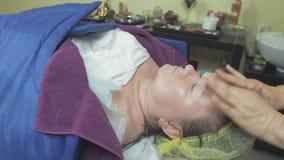 Cosmetologisten gör massage av pannan till den vuxna tjocka kvinnan i skönhetsalong stock video