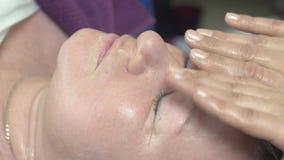 Cosmetologisten gör massageframsidan den feta kvinnan i skönhetsalong slå Anti-ålder arkivfilmer