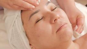 Cosmetologisten gör ren huden av framsidan av en asiatisk medelålders kvinna i en skönhetsalong Kosmetiskt tillv?gag?ngss?tt f?r  arkivfilmer
