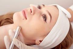 Cosmetologisten gör tillvägagångssättet Microdermabrasion av den ansikts- huden av en härlig ung kvinna i en skönhetsalong royaltyfri bild
