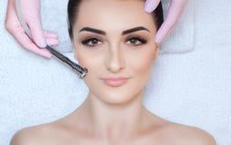 Cosmetologisten gör tillvägagångssättet Microdermabrasion av den ansikts- huden av en härlig ung kvinna i en skönhetsalong fotografering för bildbyråer