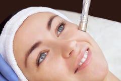Cosmetologisten gör tillvägagångssättet Microdermabrasion av den ansikts- huden av en härlig ung kvinna i en skönhetsalong arkivfoto