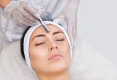 Cosmetologisten gör tillvägagångssättet Microdermabrasion av den ansikts- huden av en härlig ung kvinna royaltyfria bilder