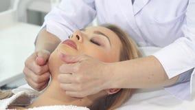 Cosmetologisten masserar framsidan för klient` s royaltyfri bild