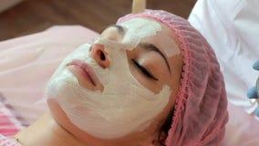 Cosmetologisten sätter en maskering på framsidan av en härlig kvinna med en borste arkivfilmer