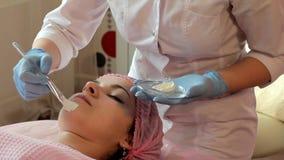 Cosmetologisten sätter en maskering på framsidan av en härlig kvinna med en borste stock video