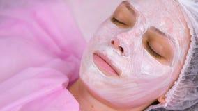 Cosmetologisten sätter maskeringen på kvinnans framsida med borsten Fukta framsidan tätt med textsidan upp arkivfilmer