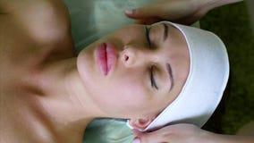 Cosmetologisten sätter på huvudbindeln på ung kvinna för behandling i brunnsortsalong stock video
