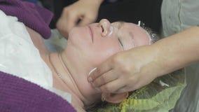 Cosmetologistwipeframsida av kvinnan i skönhetsalong vid bomullsblocket efter algmaskering stock video