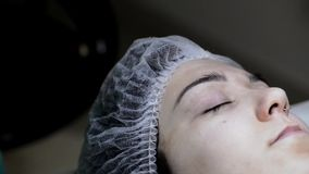 Cosmetologo che applica trucco permanente sul tatuaggio del sopracciglio-sopracciglio video d archivio