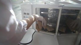 Cosmetologo che apre pacchetto sterile con il pezzo della mano di microdermabrasion e che prepara l'attrezzatura per un trattamen stock footage