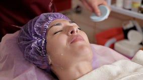 Cosmetologo che rimuove la maschera dell'alginato dalla giovane donna archivi video