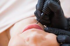 Cosmetologo dell'estetista che applica trucco permanente su girl& x27; fronte di s immagini stock