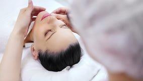 Cosmetologo femminile medico dell'angolo alto che fa massaggio facciale di contorno alla giovane ragazza affascinante stock footage