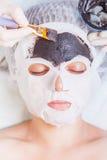 Cosmetologo nel salone della stazione termale che applica la maschera di protezione del fango facendo uso della spazzola Fotografie Stock Libere da Diritti