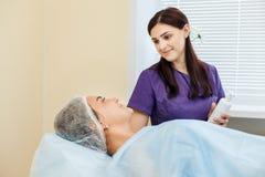 Cosmetology der Doktor berät den Patienten im Schönheitssalon Stockbilder