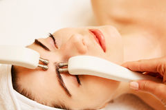 cosmetology Härlig kvinna på det Spa klinikhälerit som stimulerar elektrisk ansikts- behandling från terapeuten Closeup Of arkivbild