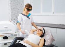 cosmetology Het ultrasone gezicht schoonmaken, die in een schoonheidssalon pellen Mooie Vrouw die de Gezichtscavitatie van de Hui Stock Afbeelding