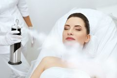 cosmetology Kvinna på ansikts- syre Cryotherapy på skönhetmitten fotografering för bildbyråer