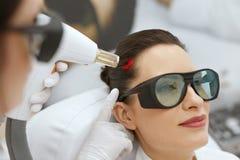 cosmetology Kvinna på behandling för stimulans för hårtillväxtlaser royaltyfri bild