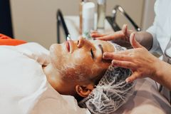 cosmetology La donna sta avendo maschera di protezione in gabinetto di cosmetologia Immagini Stock
