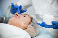 Cosmetology procedures. Peeling treatment. Smearing cream on the face. Patient smiling. Close up