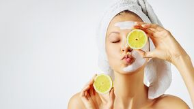 Free Cosmetology, Skin Care, Face Treatment, Spa And Natural Beauty Concept. Woman With Facial Mask Holds Lemons Stock Images - 170798634
