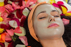 Cosmetology spa facial. Beautiful brunette in a spa salon. Girl lying on petals of roses in a beauty salon.Cosmetology, beautician, beautiful background Stock Photography