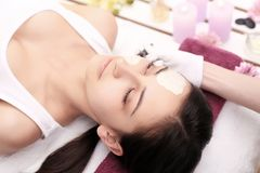 Cosmetology spa facial. Beautiful brunette in a spa salon stock photography