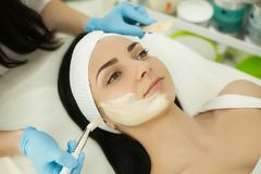 Woman receiving professional brush peeling in the cosmetology of. Cosmetology. Ultrasonic face cleaning, peeling, in a beauty salon royalty free stock photos