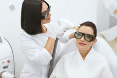 Cosmetology. Woman At Hair Growth Laser Stimulation Treatment royalty free stock photos