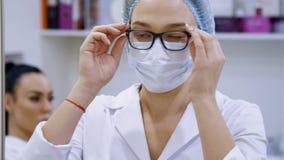 Cosmetologyraum in der Klinik, die tragenden Gläser einer Ärztin, eine weiße Uniform tragend, kleidet eine medizinische Kappe und stock video footage