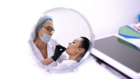 Cosmetologyraum in der Klinik, eine Ärztin in der weißen Form, Hyaluronsäure in die geduldigen ` s Lippen einspritzend prozedur stock video
