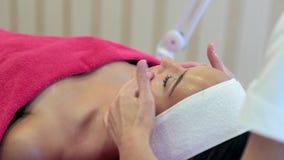 Cosmetologytillvägagångssätt Närbild av en ung kvinna som får Spa behandling lager videofilmer