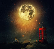 The cosmic call. Imaginary view as a young man sitting on the cliff, wait for someone to call him at the phone booth box. Full moon night with a starry sky Stock Photography