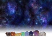 Cosmic Chakra Healing Stones. A row of chakra colored tumbled healing crystals set against a background of the Universe providing copy space above royalty free stock photos