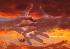 Cosmic connections. Reaching hands in a sunset background Stock Photos