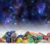 Cosmic Healing Crystals. Deep space background with stars, suns and planets with a selection of multicolored tumbled healing crystals at the front and plenty of stock images