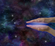 Cosmic Healing Energy. Healer's parallel hands showing blue electromagnetic aura on a deep space background with plenty of copy space royalty free stock photography