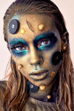 Cosmic unusual makeup with decorative elements on face, golden skin stock image