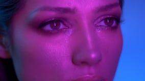 Cosmical moda model w purpurowych neonowych światłach rusza się wolno i ogląda uważnie spokojnie rightwards w studiu i zbiory