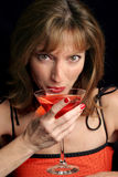 Cosmo Girl Takes A Sip. A beautiful woman in red sipping a cosmopolitan Stock Photography