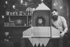 Cosmonautics. Rocket launch concept. Kid happy sit in cardboard hand made rocket. Boy play with dad, father, little. Cosmonaut sit in rocket made out of stock image