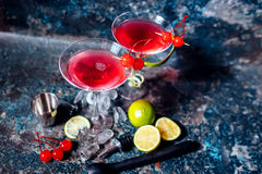 Cosmopolitan alcoholic cocktail drink at casino and bar served with lime, ice and cherries Stock Photos