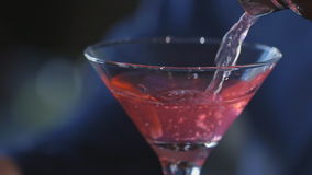 A Cosmopolitan being poured into a cocktail glass stock footage